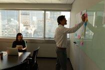 Vista laterale dei dirigenti ufficio attento giovane bello lavorare in un ufficio moderno. Collega di razza mista in background — Foto stock