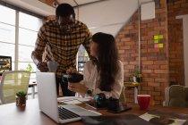 Фронтальный взгляд различных бизнесменов, обсуждающих друг с другом в офисе — стоковое фото