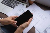 Vista de alto ângulo de empresária de raça mista, usando o celular no escritório na mesa — Fotografia de Stock