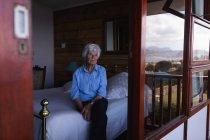 Vorderansicht einer nachdenklichen aktiven Seniorin, die auf dem Bett sitzt und zu Hause durch das Fenster im Schlafzimmer schaut — Stockfoto