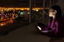 Вид сбоку на красивую молодую представительницу смешанной расы с цифровым планшетом, смотрящим в окно современного офиса — стоковое фото