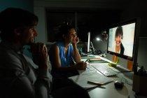 Seitenansicht glücklicher junger multiethnischer Büroleiter, die Videokonferenzen am Schreibtisch in einem modernen Büro machen — Stockfoto