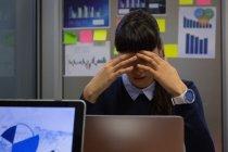 Frontansicht einer Geschäftsfrau, die deprimiert im Büro am Schreibtisch sitzt — Stockfoto