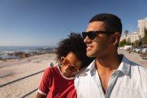 Вид спереди на афроамериканскую пару, прогуливающуюся и наслаждающуюся у моря, глядя на хобби — стоковое фото