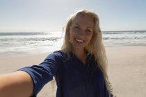 Вид спереди красивой блондинки, стоящей на пляже в солнечный день. Она делает селфи. — стоковое фото
