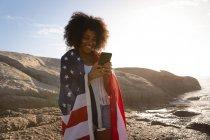 Vue de face de la femme afro-américaine debout et utilisant un téléphone portable avec drapeau américain près de la mer — Photo de stock