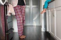 Низкая Секция смешанной расы матери и дочери вместе в комнате кухня дома — стоковое фото