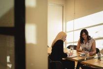 Vista frontale delle donne d'affari che notano e lavorano su tablet digitale alla conferenza dell'ufficio — Foto stock