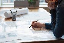 Parte média do empresário de pé e trabalhando sobre o projeto na conferência de escritório — Fotografia de Stock