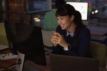 Vista frontal de la mujer de negocios asiática sonriendo mientras mira el ordenador en la oficina - foto de stock