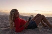 Vista laterale della donna bionda che utilizza il telefono cellulare mentre si trova in spiaggia. Lei è sdraiata sulla sabbia — Foto stock