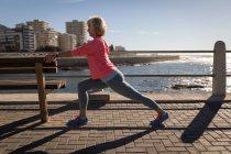 Боковой вид активной пожилой женщины, растянувшейся на скамейке на набережной рядом с морем в лучах солнца — стоковое фото