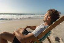 Вид сбоку молодого человека, отдыхающего на солнцепеке на пляже. Он сидит лицом к океану — стоковое фото