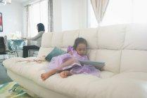 Фронтальний вид змішаної раси дочки, використовуючи цифровий планшетний при матері носити хіджаб, працює над ноутбуком у фоновому режимі у вітальні на дому — стокове фото