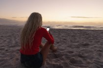 Rear view of blonde Caucasian woman using mobile phone at beach. She is sitting on the sand — Stock Photo