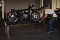 Вид збоку Кавказького велосипеда механік ремонт велосипеда в гаражі — стокове фото