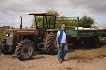 Vue latérale d'un agriculteur masculin caucasien âgé s'éloignant du tracteur à la ferme par une journée ensoleillée — Photo de stock