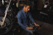 Высокий угол обзора белого механика велосипедов с помощью ноутбука в гараже — стоковое фото