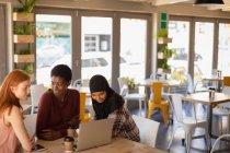 Вид сбоку на молодых подруг смешанной расы, взаимодействующих друг с другом, используя ноутбук в кафе — стоковое фото