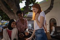 Вид спереди счастливых подруг смешанной расы, пользующихся мобильным телефоном, сидя на скамейке под деревом — стоковое фото