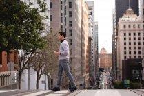 Vista lateral del hombre asiático cruzando la calle mientras toma café - foto de stock