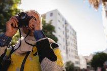 Низький кут зору змішаної раси жінка зйомки з її цифровою камерою на вулиці в сонячний день — стокове фото