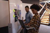 Вид сбоку на молодую деловую женщину смешанной расы с помощью ноутбука, в то время как бизнесмен смешанной расы стоит рядом с графиком в современном офисе — стоковое фото