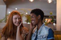 Vista frontale delle amiche miste che ascoltano musica con auricolare al ristorante — Foto stock
