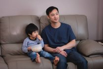 Front view of a happy Asian father and son sitting on sofa and eating popcorn while watching TV at home — Stock Photo