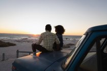 Rear view of romantic couple sitting on a car at beach during sunset — Stock Photo