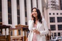 Вид на щасливу азіатській жінці, яка розмовляє на мобільному телефоні, маючи каву на вулиці — стокове фото