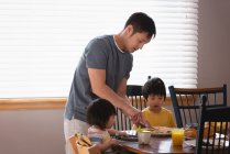 Vue latérale d'un père asiatique servant le petit déjeuner à ses enfants à la table à manger dans la cuisine à la maison — Photo de stock