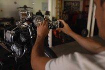 Задний вид созревшего кавказского мотомеханика, снимающего велосипед в гараже — стоковое фото