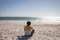 Вид на молодого афроамериканца, отдыхающего на пляже в солнечный день — стоковое фото