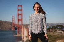 Ritratto di bella donna sorridente e in piedi vicino al ponte sospeso — Foto stock