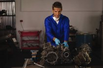 Вид на молодий Кавказький чоловік велосипед механік ремонту велосипеда двигуна в гаражі — стокове фото