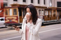 Front view of thoughtful Asian woman using mobile phone while having coffee at street — Stock Photo