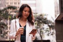 Vorderansicht einer asiatischen Frau, die auf der Straße steht und ihr Handy benutzt — Stockfoto