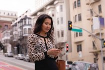 Side view of Asian woman using mobile phone while standing on street — Stock Photo