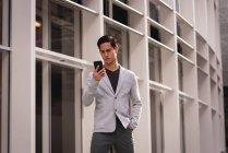 Vorderansicht eines hübschen asiatischen Mannes, der sein Handy benutzt, während er in der Nähe eines Gebäudes steht — Stockfoto