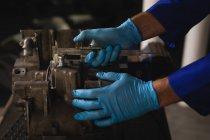 Side view of bike mechanic repairing bike engine in garage — Stock Photo