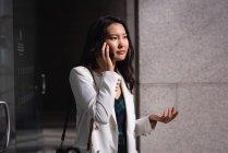 Vista laterale della donna asiatica che parla sul telefono cellulare mentre si trova in corridoio — Foto stock
