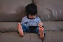 Vista dianteira de um menino asiático pequeno que usa a tabuleta digital ao sentar-se no sofá em casa — Fotografia de Stock
