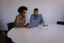 Vista frontal de jovens empresários de raça mista discutindo sobre laptop na mesa no escritório moderno — Fotografia de Stock