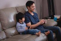 Vista lateral de feliz padre asiático e hijo jugando juntos en los videojuegos mientras están sentados en el sofá en casa - foto de stock