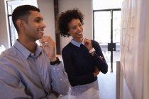 Боковой вид счастливых Смешанные гонки деловых людей, глядя на планы придерживаться на стене в то время как. Они касаются подбородка в офисе — стоковое фото