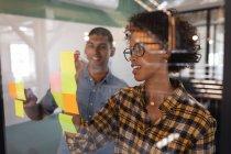 Вид спереди счастливых бизнесменов смешанной расы, пишущих на липких нотах, стоящих в современном офисе — стоковое фото