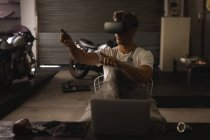 Vue de face du mécanicien masculin caucasien utilisant un casque de réalité virtuelle dans le garage — Photo de stock