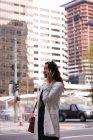 Vue latérale de la femme asiatique parlant sur un téléphone portable tout en se tenant sur la rue — Photo de stock