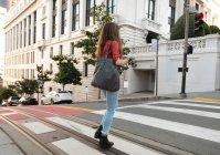 Vista laterale della donna in piedi sulla zebra che attraversa la strada — Foto stock